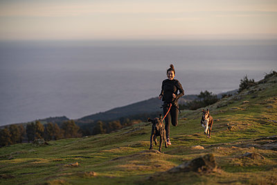 Female runner running with dogs in canicross style on hill - p300m2282819 by SERGIO NIEVAS