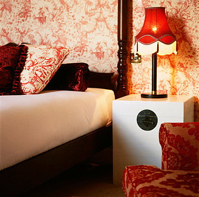 Red and white bold patterned wallpaper with red decor and a double bed in a bedroom - p349m695113 by Emma Lee
