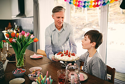 Boy blowing candles while grandfather holding birthday cake at table during party - p426m1580220 by Maskot