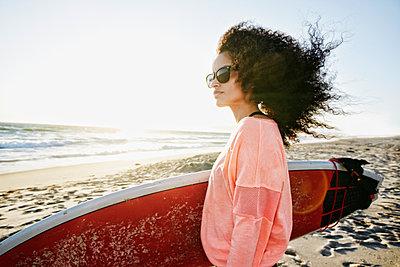 Hispanic woman holding surfboard at beach - p555m1303382 by Peathegee Inc
