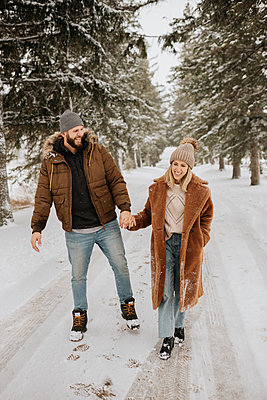 Canada, Ontario, Smiling couple holding hands on winter walk - p924m2271212 by Sara Monika
