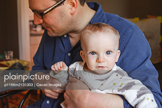 a bright-eyed baby sits in his father's lap at a dining room table - p1166m2131303 by Cavan Images