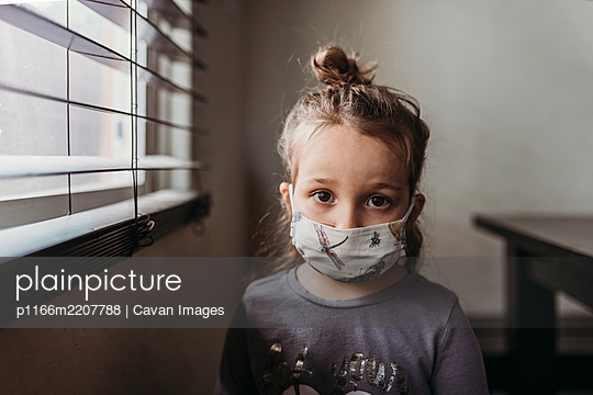 Close up portrait of preschool age girl with mask on looking at camera - p1166m2207788 by Cavan Images