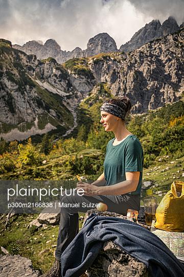 Woman on a hiking trip at Wilder Kaiser having a break, Kaiser mountains, Tyrol, Austria - p300m2166838 von Manuel Sulzer