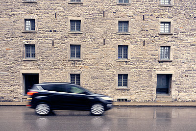Abstract of car driving along road with stone walled building behind, Montreal, Quebec, Canada, 2019 - p1362m2117378 by Charles Knox
