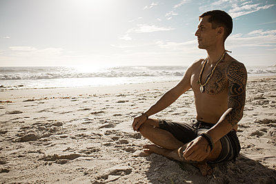 Mann meditiert auf dem Strand im Sonnenschein - p1640m2261020 von Holly & John