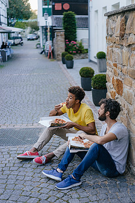 Two friends eating takeaway pizza in the city - p300m1535203 by Kniel Synnatzschke