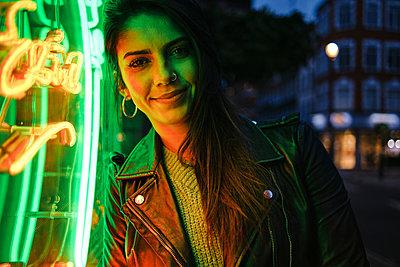 Beautiful woman with jacket standing by illuminated light - p300m2273699 by Angel Santana Garcia