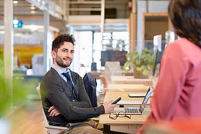 Smiling businessman with mobile phone looking at female colleague in office - p300m2281694 by Emma Innocenti