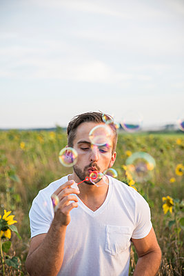 Man blowing bubbles in field - p352m1523847 by Lotta Johansson