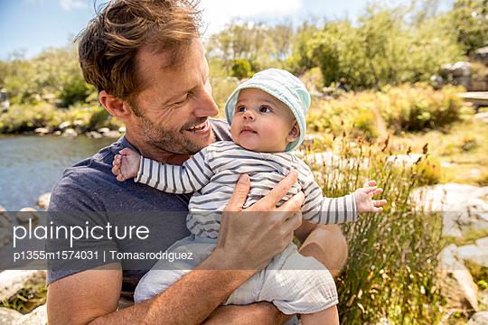 Vater und Baby am Seeufer - p1355m1574031 von Tomasrodriguez