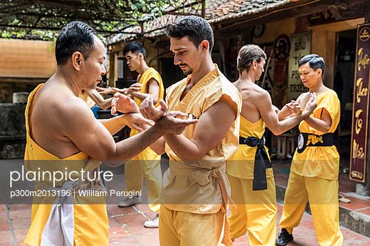 Vietnam, Hanoi, men exercising kung fu, european man learning kung fu - p300m2013196 von William Perugini