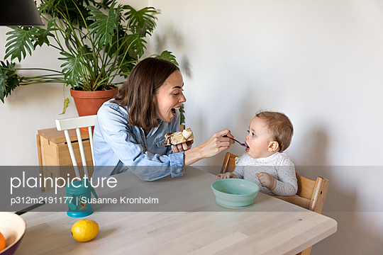 Mother feeding baby at table - p312m2191177 by Susanne Kronholm