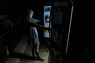 Young adult woman in dark kitchen looks into open refrigerator - p1166m2129654 by Cavan Images