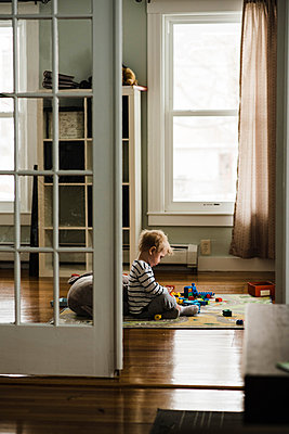 Little boy playing by himself - p1166m2159582 by Cavan Images