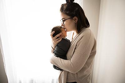 Backlit Gen Z Hipster Mom Kisses Newborn Baby in Front of Window - p1166m2212285 by Cavan Images