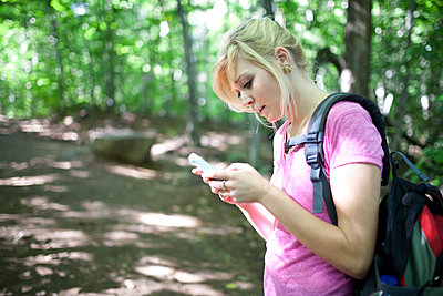 Young woman hiking while using mobile phone - p1362m2062202 by Charles Knox