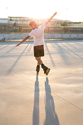 Man with rollerblades and arms extended at sunset - p300m1175955 by Andrés Benitez