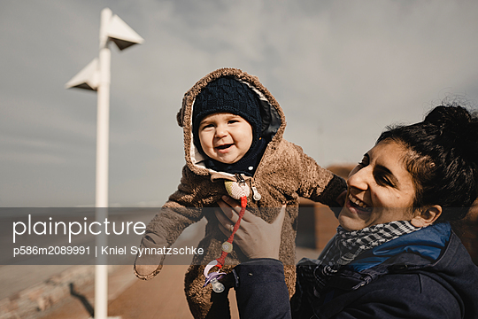 Mother holds daughter in her arms - p586m2089991 by Kniel Synnatzschke