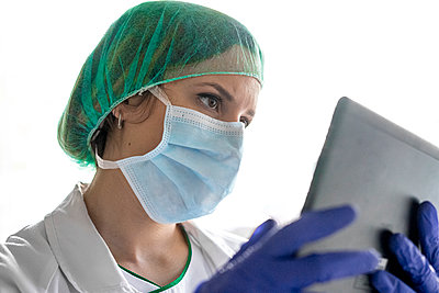 unrecognizable female nurse using a digital tablet while standing in a hospital. - p1166m2190780 by Cavan Images