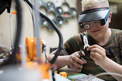 Female electronics engineer with pliers at 3d printer in workshop - p1192m1202131 by Hero Images