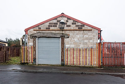 The end of a block built single storey building with a steel roller door and painted fence. - p1302m1223566 by Richard Nixon