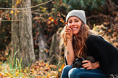 Smiling beautiful woman holding leaves while sitting with camera at forest during autumn - p300m2276965 by Manu Reyes