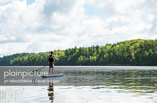 Teen boy paddling on a SUP on lake in Ontario, Canada on a sunny day. - p1166m2208004 by Cavan Images