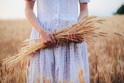 Midsection of woman holding wheat crops while standing on field against sky - p1166m1546994 by Cavan Images