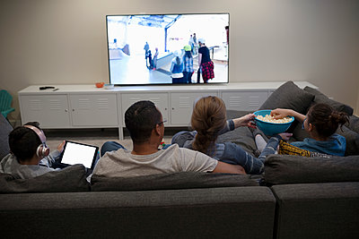 Family watching movie, eating popcorn on sofa - p1192m2094615 by Hero Images