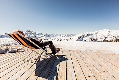 Austria, Damuels, senior man relaxing in deckchair on sun deck in winter landscape - p300m1505584 by Nullplus
