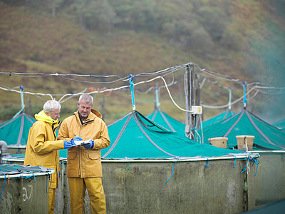 Workers talking at fish farm - p42917342f by Monty Rakusen