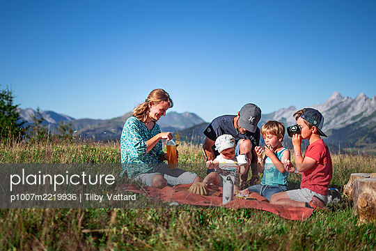 Family has a picnic in the mountains, France - p1007m2219936 by Tilby Vattard