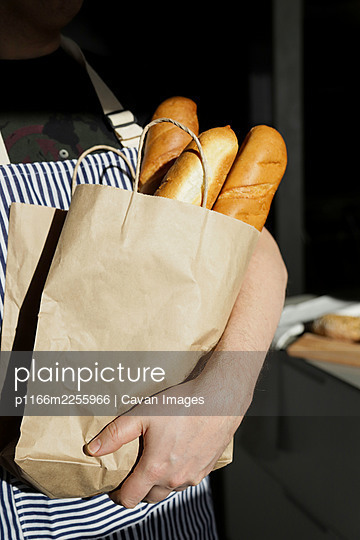 A man holding a bag of baguettes - p1166m2255966 by Cavan Images