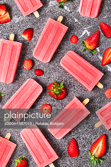 Homemade strawberry ice lollies and strawberries on marble - p300m1587013 von Retales Botijero