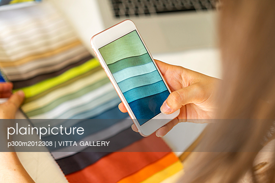 Fashion designer taking pictures of fabric samples with ger mobile phone - p300m2012308 von VITTA GALLERY