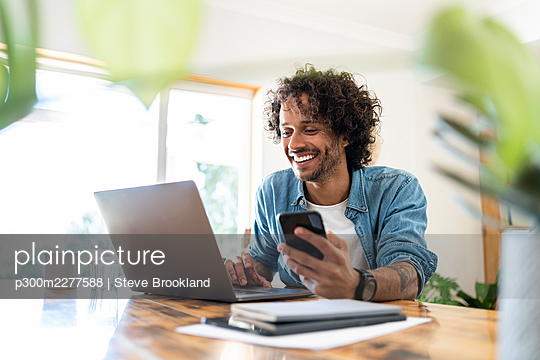Smiling male professional holding smart phone while using laptop on table at home - p300m2277588 by Steve Brookland