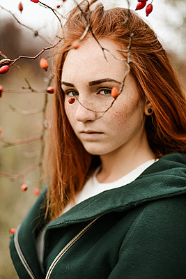 Thoughtful teenage girl with red head standing amidst plants - p1166m2113123 by Cavan Images
