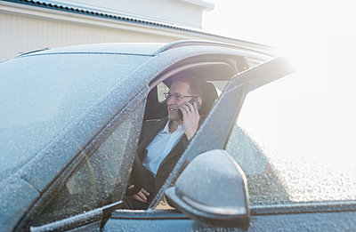 man sat in his frosty car talking on the phone leaving for work - p1166m2148549 by Cavan Images