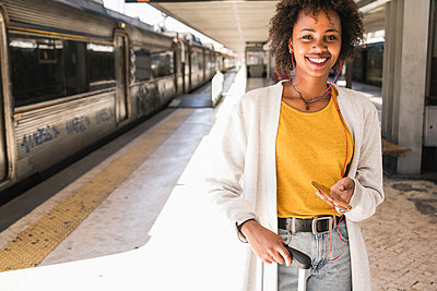 Portrait of smiling young woman with earphones and smartphone at platform - p300m2156732 by Uwe Umstätter