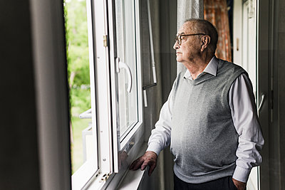 Pensive senior man looking out of window - p300m2189168 by Uwe Umstätter