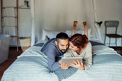 Couple using digital tablet while lying on bed at home - p300m2221091 by Javier Sánchez Mingorance
