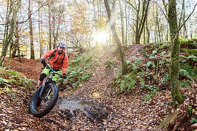Caucasian man steering bicycle around mud puddle - p555m1491074 by Kolostock