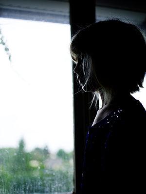 Girl looking through the window - p945m1467742 by aurelia frey