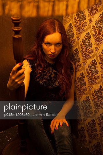 Frau sitzt in Ecke unter Lampenschirm - p045m1208460 von Jasmin Sander