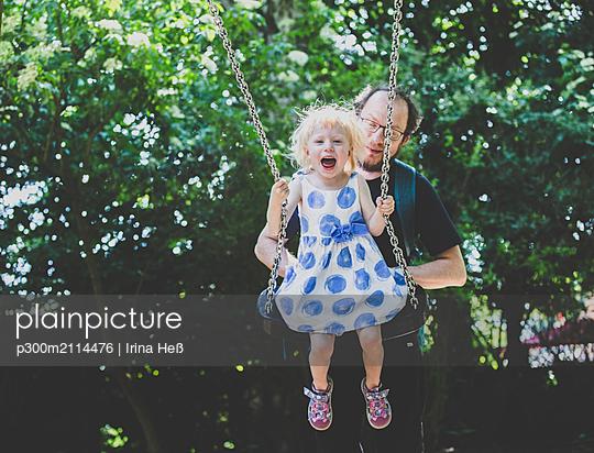 Father pulling swing with girl at playground - p300m2114476 von Irina Heß