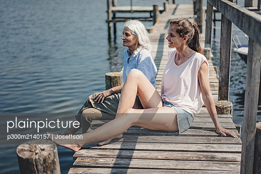 Mother and daughter sitting on jetty, relaxing at the sea - p300m2140157 by Joseffson