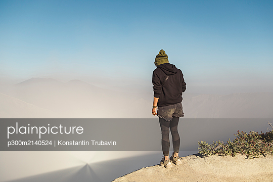 Young woman standing at the edge of volcano Ijen, Java, Indonesia - p300m2140524 by Konstantin Trubavin