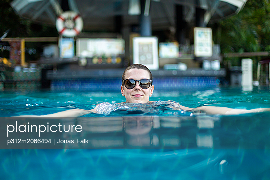 Young woman relaxing in swimming pool - p312m2086494 by Jonas Falk