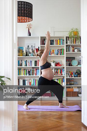 plainpicture - plainpicture p795m1584131 - Pregnant woman practicing yoga - plainpicture/Janklein